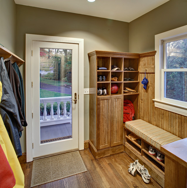 Example of a classic medium tone wood floor entryway design in New York with beige walls and a glass front door