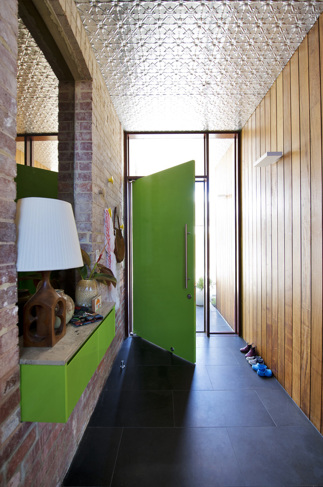 Example of a mid-sized midcentury modern black floor entryway design in Perth with a green front door