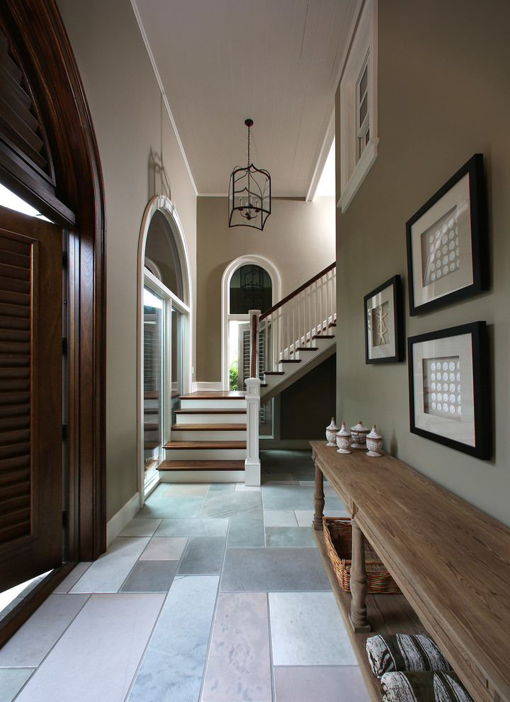 Inspiration for a tropical foyer remodel in Tampa with gray walls and a dark wood front door