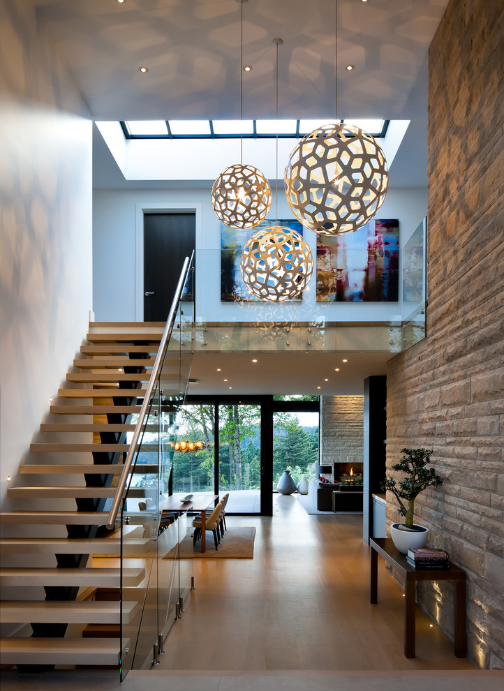 Inspiration for a contemporary light wood floor foyer remodel in Vancouver with white walls
