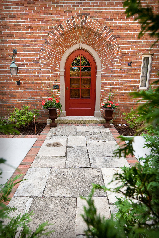 Inspiration for a mid-sized timeless entryway remodel in Milwaukee with a red front door