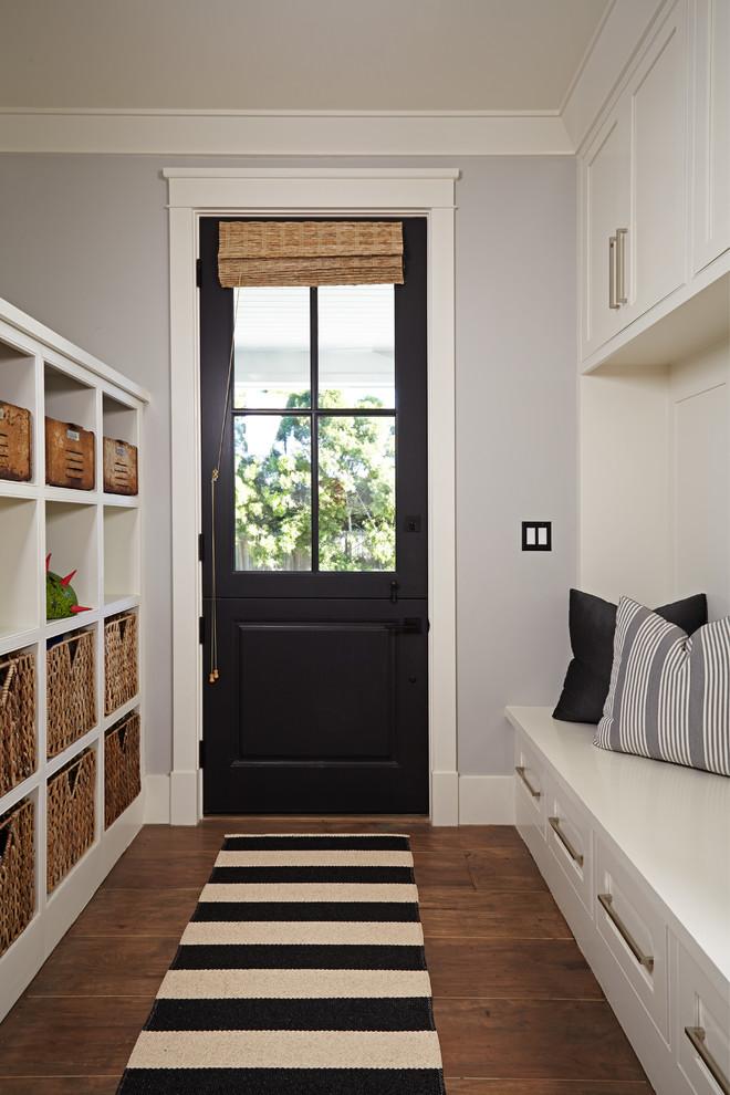 Entryway - transitional medium tone wood floor entryway idea in Orange County with gray walls and a black front door