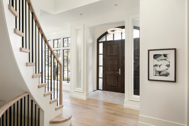 Entryway - mid-sized transitional light wood floor and beige floor entryway idea in Calgary with white walls and a dark wood front door