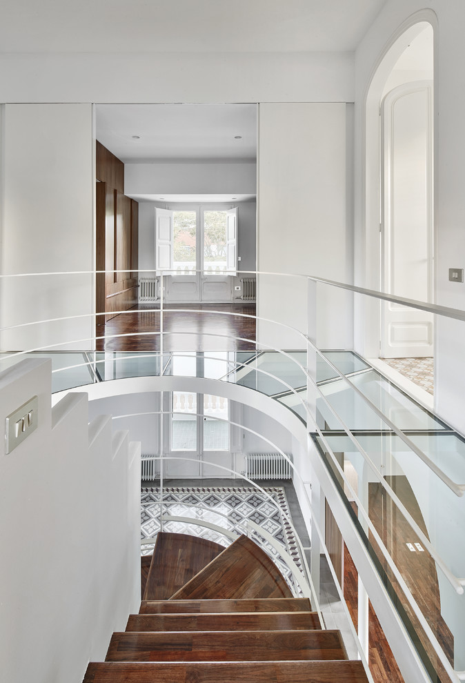 Example of a mid-sized transitional wooden curved staircase design in Barcelona