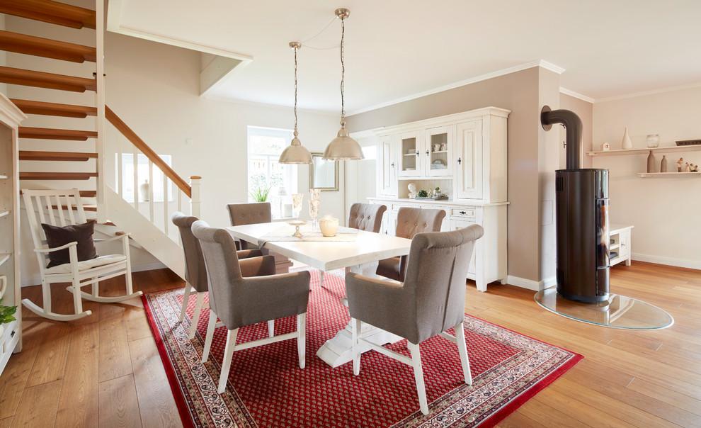 Offenes, Mittelgroßes Landhausstil Esszimmer mit weißer Wandfarbe, braunem Holzboden, Kaminofen, Kaminumrandung aus Metall und braunem Boden in Bremen