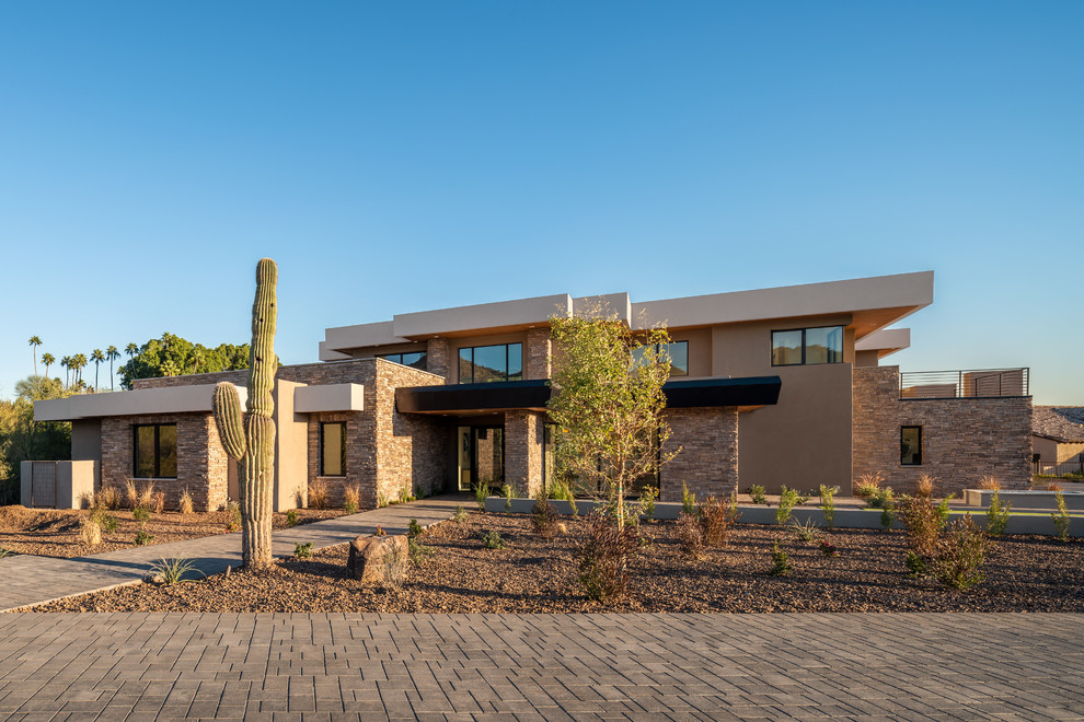 Inspiration for a southwestern beige two-story exterior home remodel in Phoenix