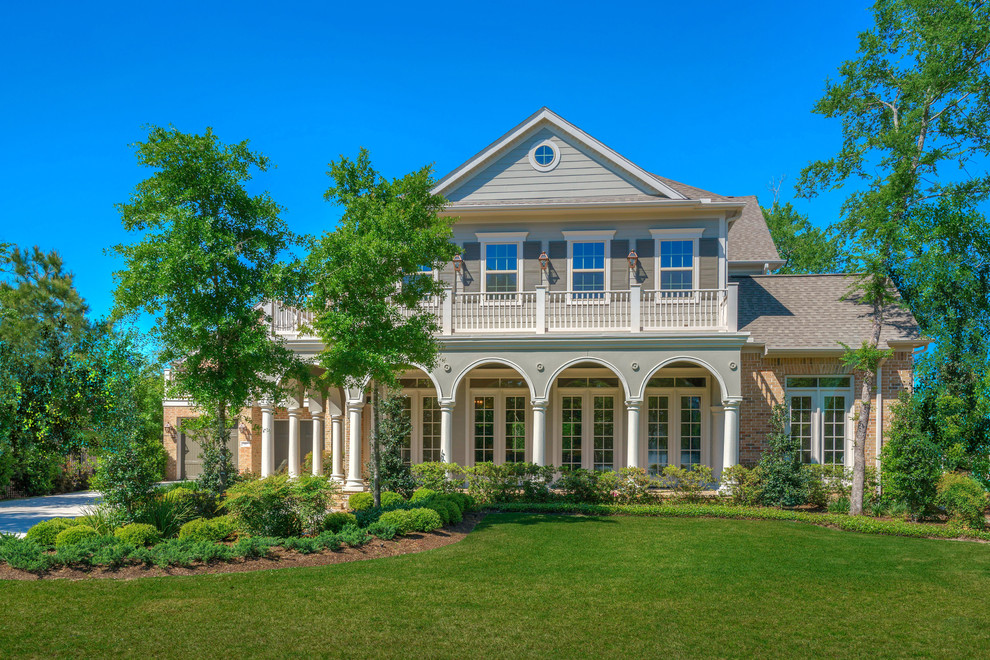 Traditional brown two-story brick exterior home idea in Houston