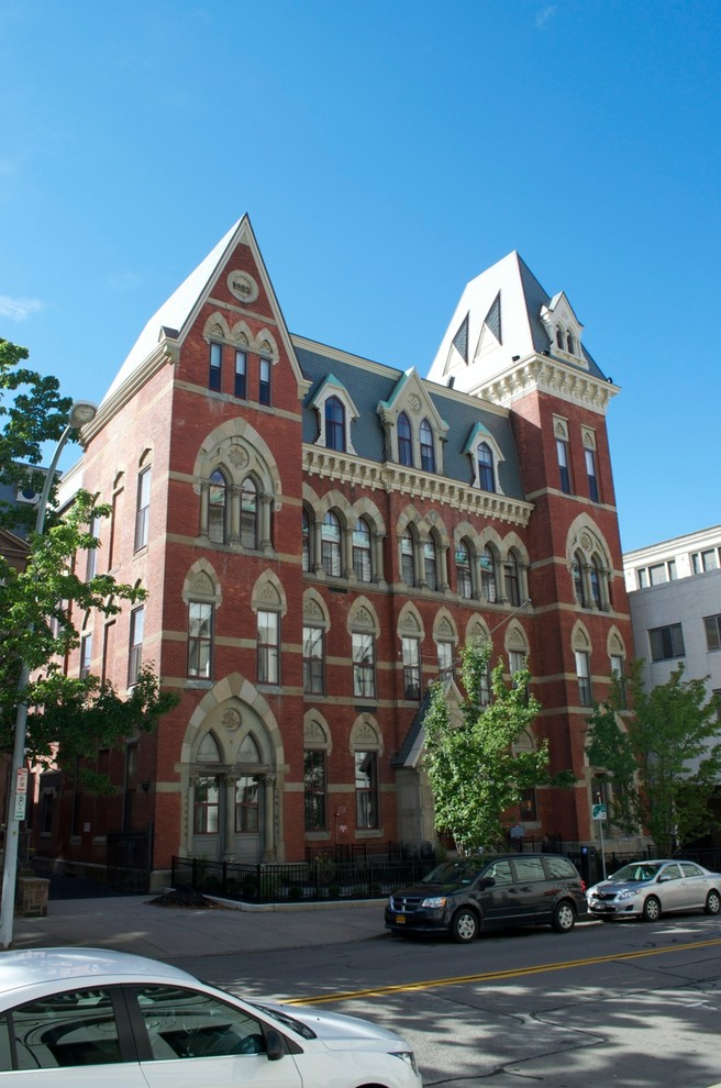 Example of a huge ornate red three-story brick apartment exterior design in New York