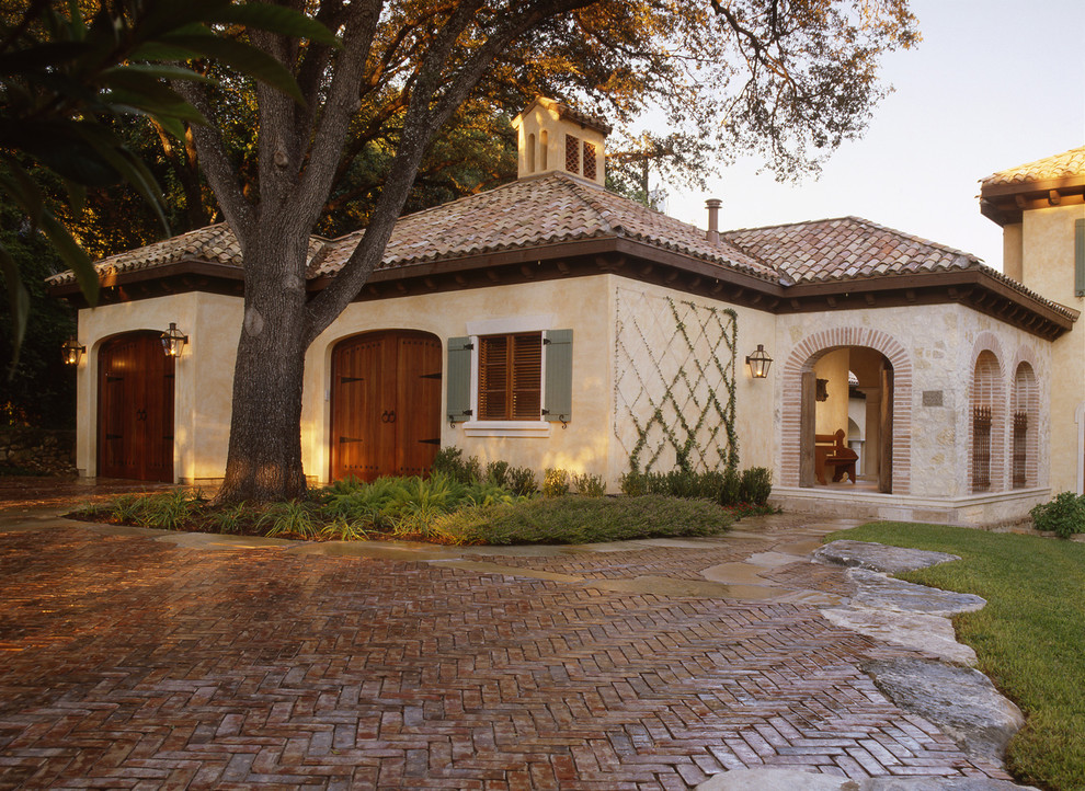 Inspiration for a mid-sized mediterranean beige two-story stone gable roof remodel in Austin with a shingle roof