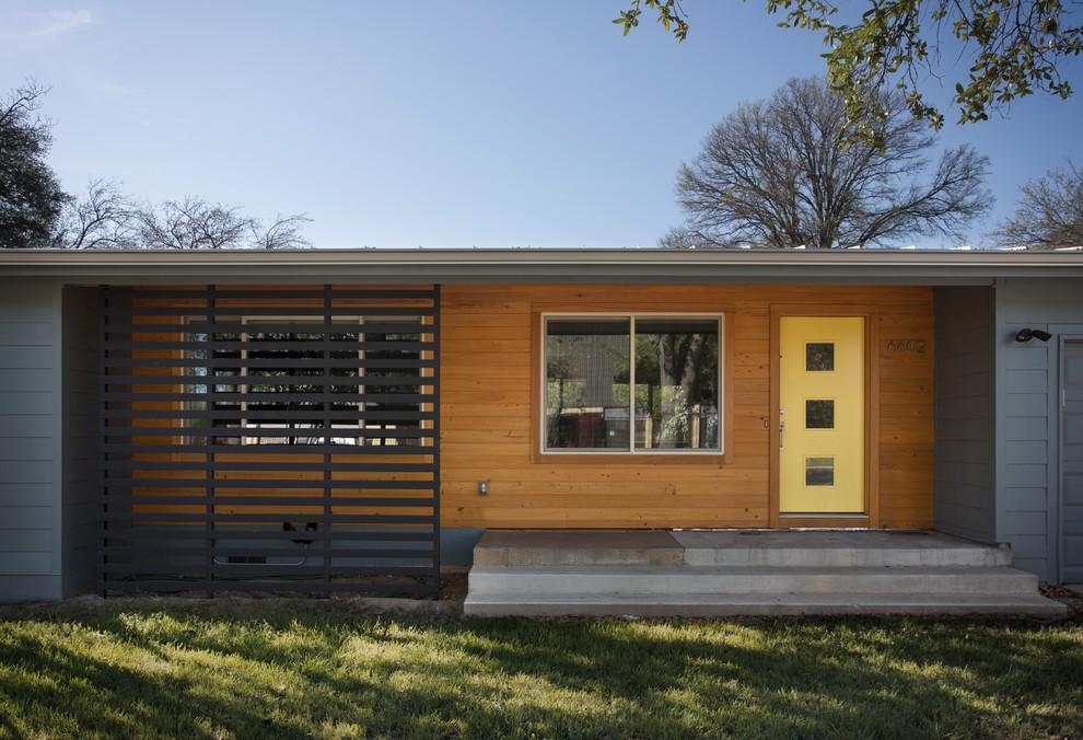 Mid-century modern gray one-story wood flat roof idea in Austin