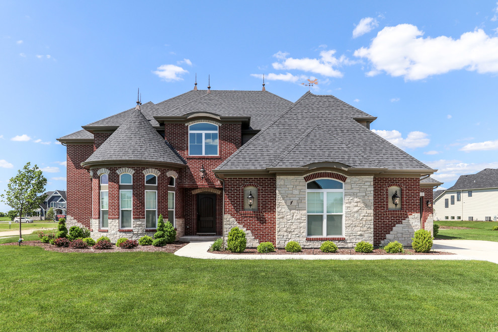 Inspiration for a large timeless red two-story stone house exterior remodel in Chicago with a hip roof