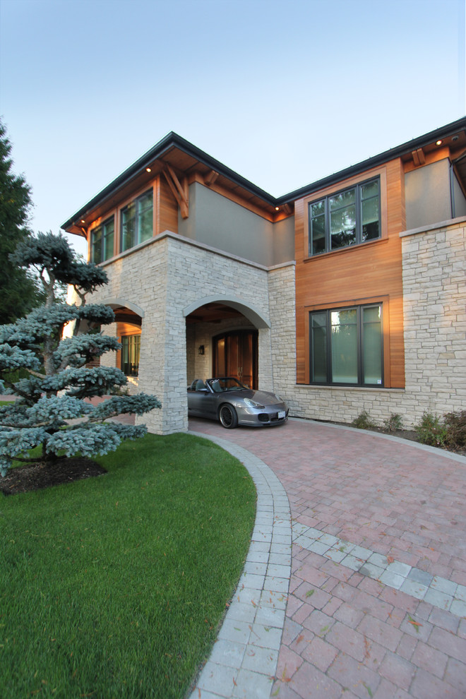 Large trendy gray two-story stone exterior home photo in Vancouver with a mixed material roof