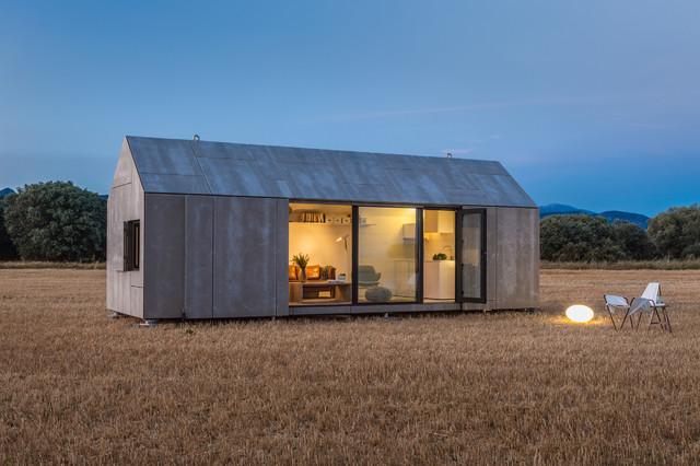Imagen de fachada gris, contemporánea, pequeña, de una planta, con revestimiento de hormigón y tejado a dos aguas