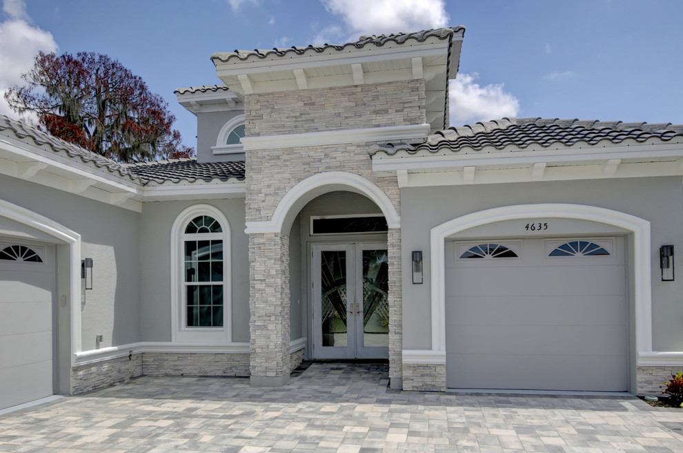 Large beach style gray two-story stucco house exterior photo in Tampa with a hip roof and a tile roof