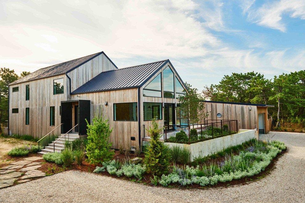 Contemporary two-story wood exterior home idea in New York with a metal roof