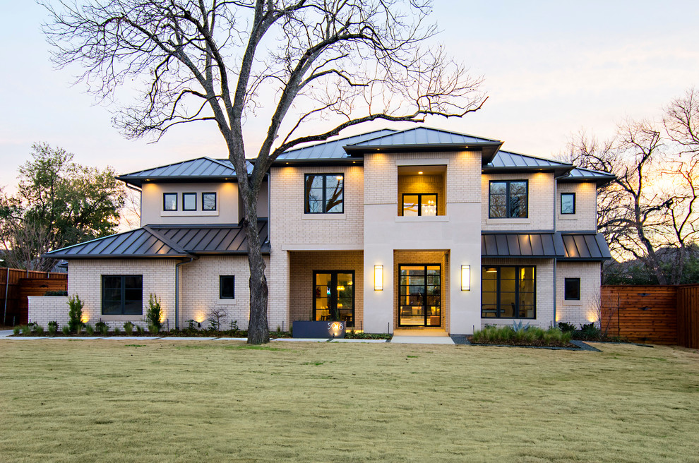 Inspiration for a transitional beige two-story brick exterior home remodel in Dallas with a hip roof and a metal roof