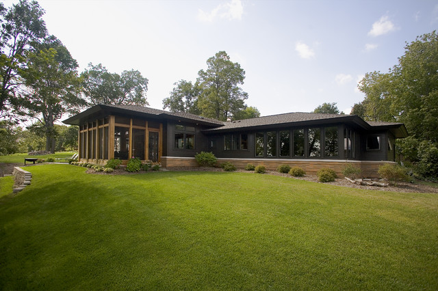 Large midcentury modern black one-story mixed siding exterior home photo in Minneapolis with a hip roof