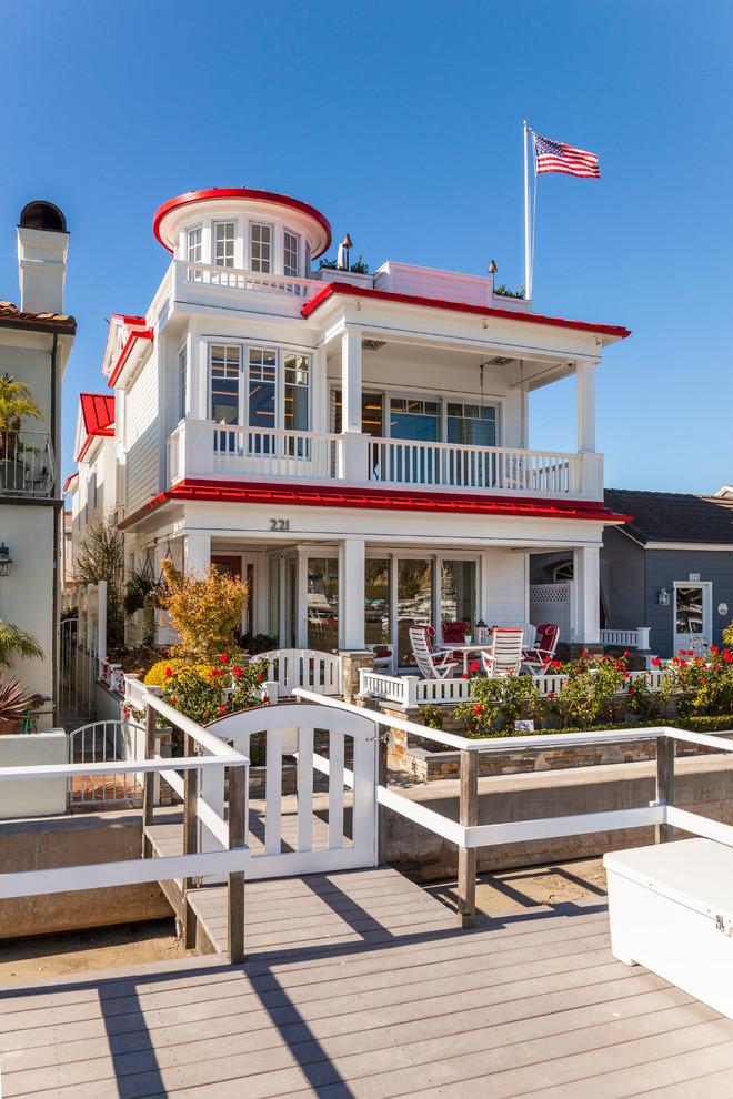 Inspiration for a coastal white three-story exterior home remodel in Orange County with a red roof