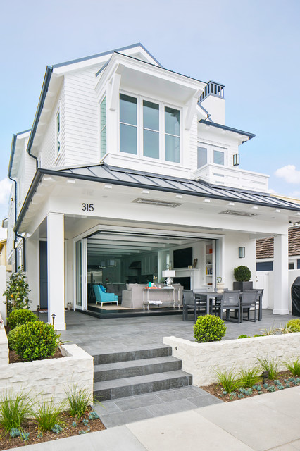 Large beach style white two-story wood exterior home idea in Orange County with a hip roof