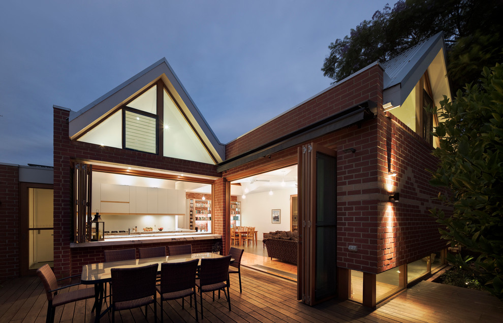 Example of a mid-sized trendy red one-story brick gable roof design in Melbourne