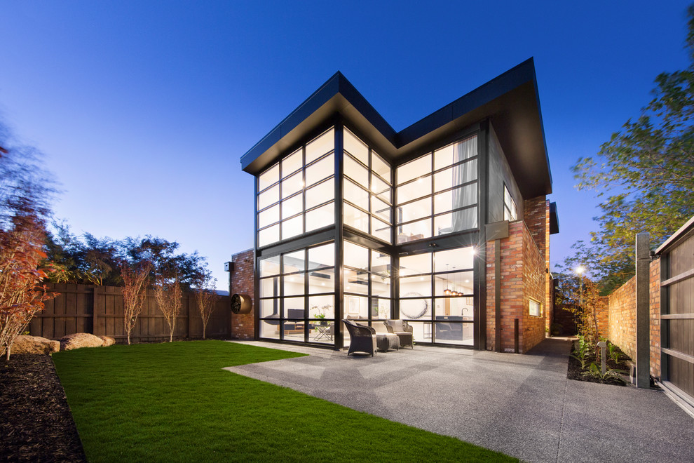 Contemporary two-story glass exterior home idea in Melbourne