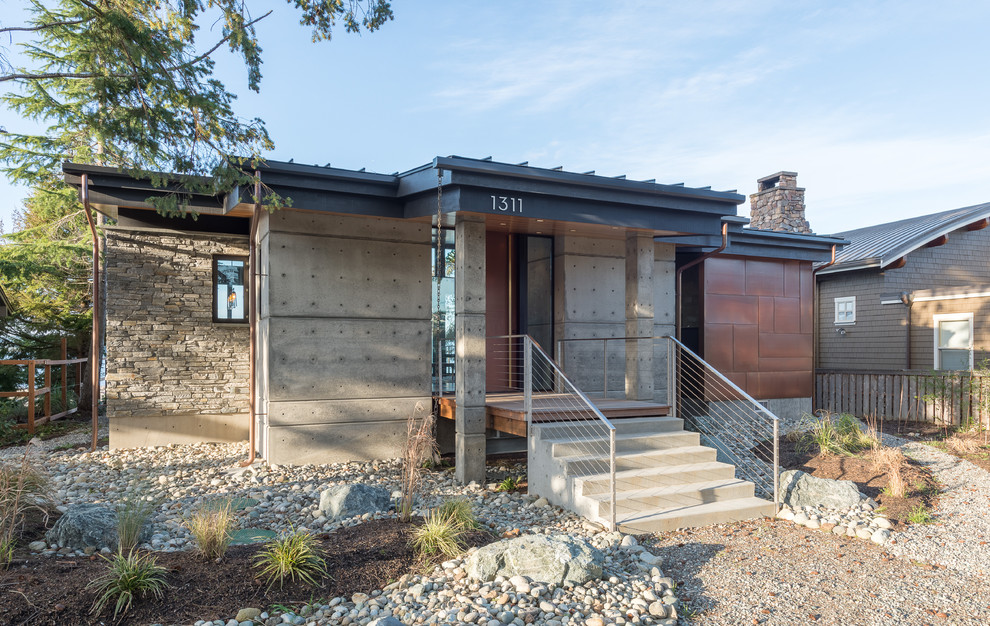 Small modern gray one-story concrete house exterior idea in Seattle with a shed roof and a metal roof