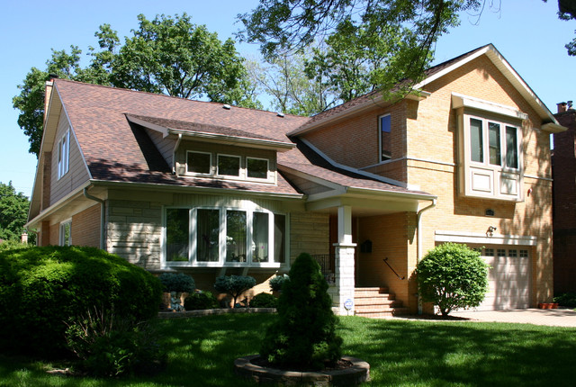 Inspiration for a mid-sized timeless beige two-story brick gable roof remodel in Chicago