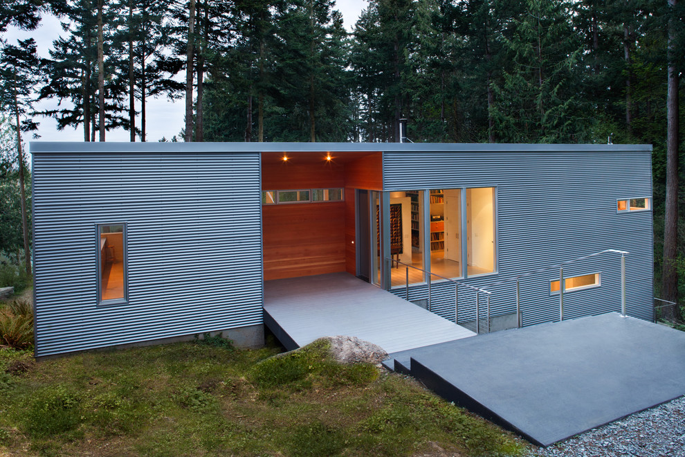 Inspiration for a mid-sized contemporary gray two-story metal flat roof remodel in Seattle
