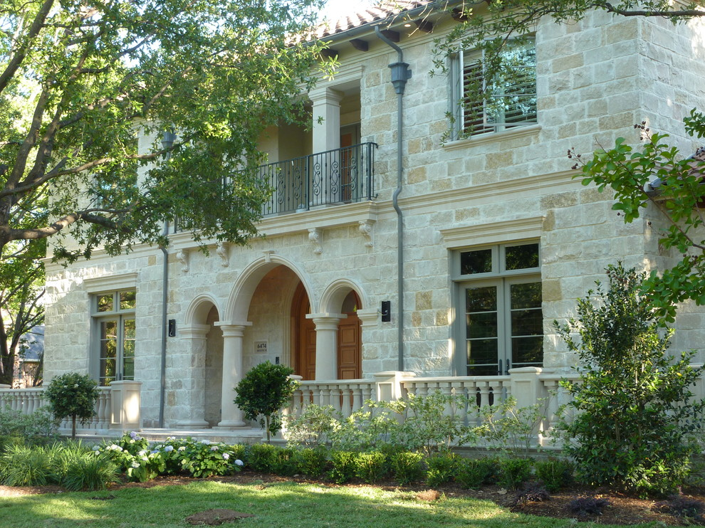 Large mediterranean beige two-story stone house exterior idea in Dallas with a hip roof and a tile roof