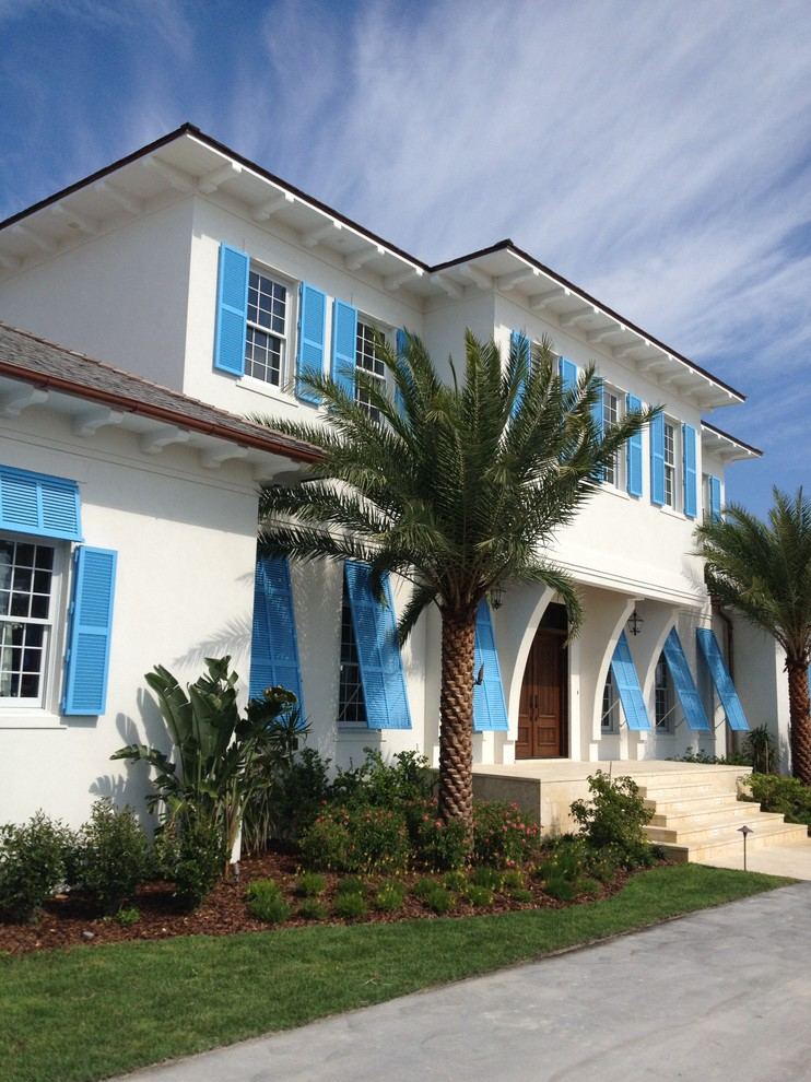 Inspiration for a large tropical white two-story stucco exterior home remodel in Tampa