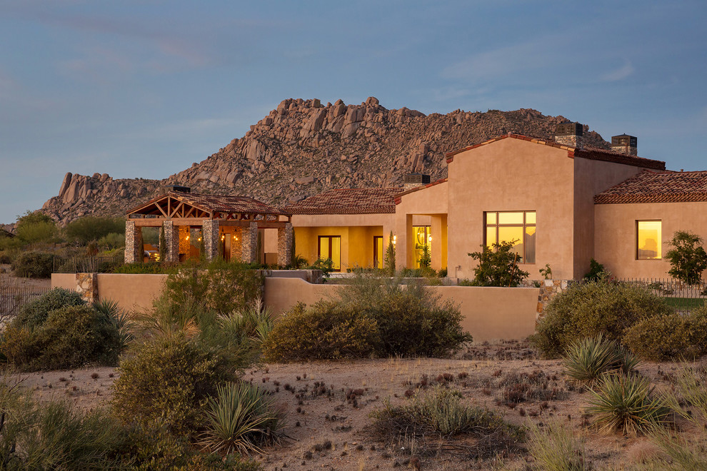Example of a huge tuscan brown one-story stucco house exterior design in Phoenix with a tile roof