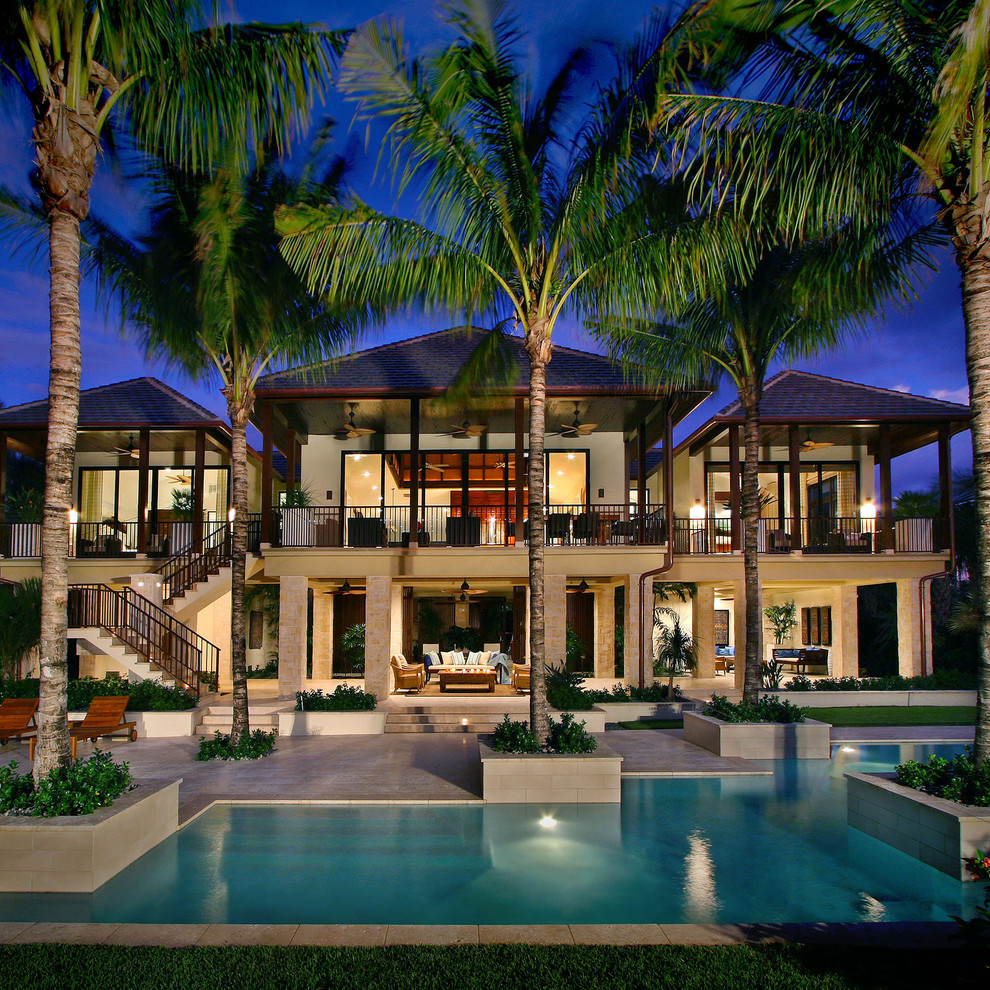 Large tropical beige two-story concrete house exterior idea in Miami with a hip roof and a shingle roof