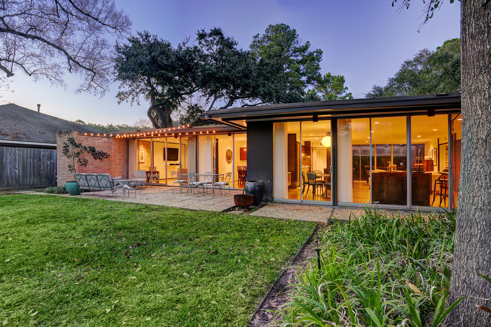 Inspiration for a large mid-century modern brown one-story brick exterior home remodel in Houston with a shingle roof