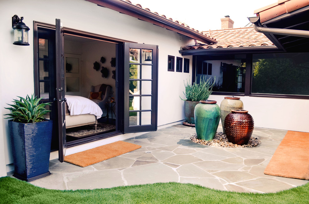 Inspiration for a large mediterranean white one-story stucco house exterior remodel in Los Angeles with a hip roof and a tile roof