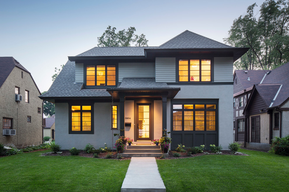 Example of a mid-sized transitional gray two-story stucco exterior home design in Minneapolis with a hip roof