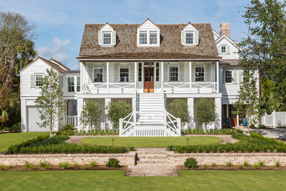 Coastal white three-story wood house exterior idea in Charleston with a hip roof and a shingle roof