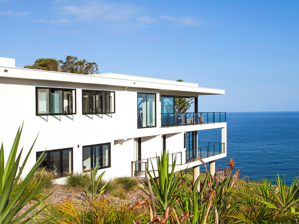 Inspiration for a small contemporary two-storey white exterior in Wollongong with concrete fiberboard siding and a flat roof.
