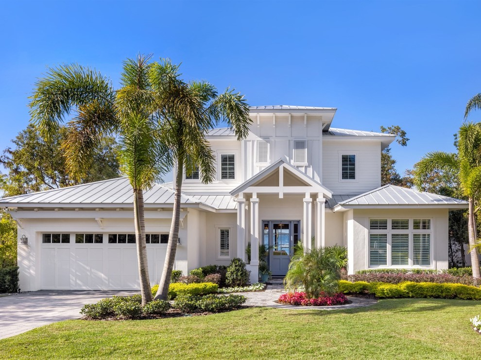 Inspiration for a coastal white two-story house exterior remodel in Orlando with a clipped gable roof