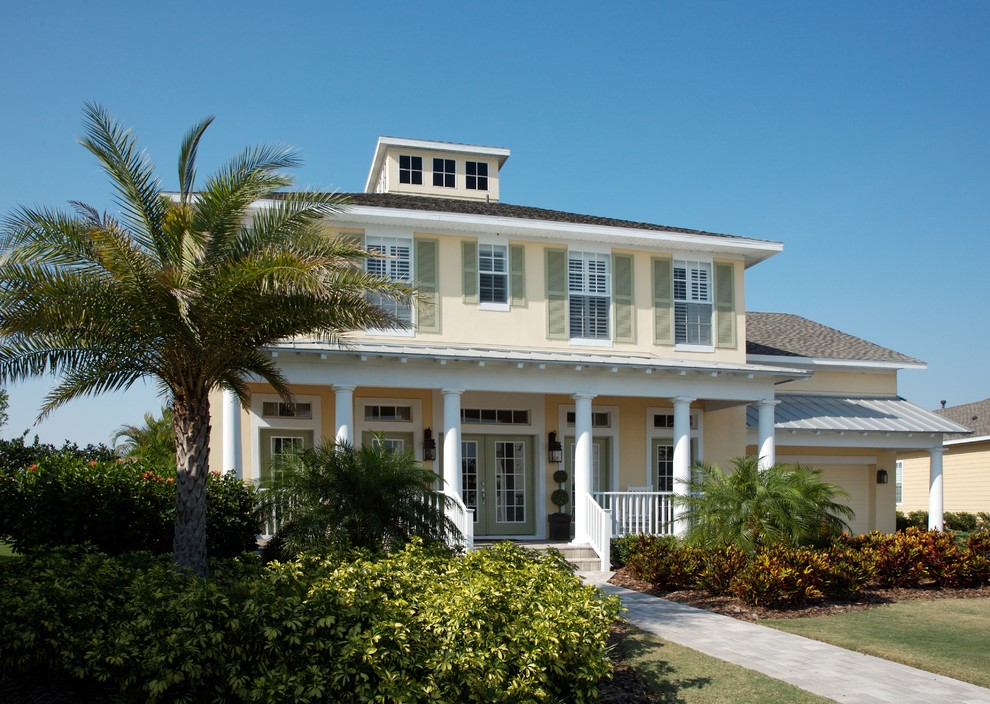 Example of a mid-sized island style yellow two-story stucco house exterior design in Tampa with a hip roof and a mixed material roof