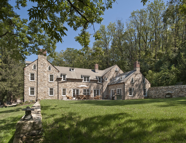 Inspiration for a large farmhouse brown three-story stone gable roof  remodel in Philadelphia with