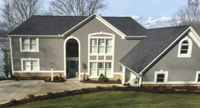Transitional gray three-story stucco exterior home idea in Other with a shingle roof