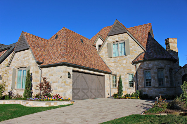 Two-story stone exterior home photo in Dallas with a hip roof
