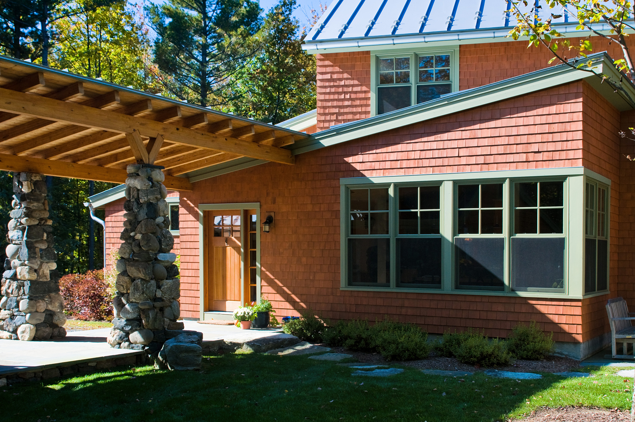 A laminated pine beam loggia connects the foyer to the garage/workshop, separating the parking area from the courtyard.