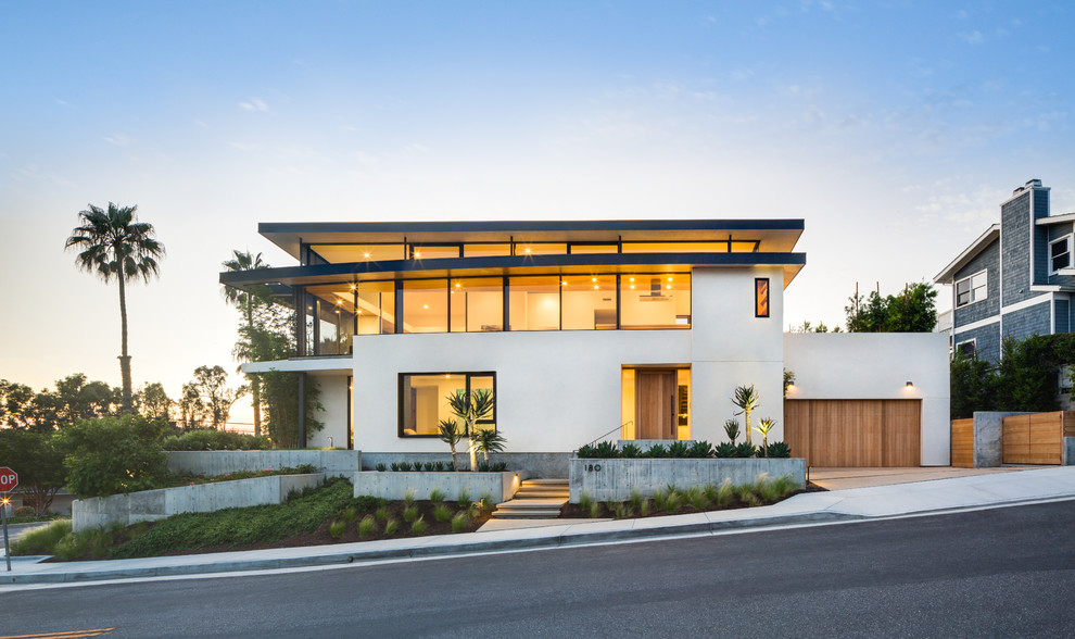 Inspiration for a large contemporary white two-story stucco exterior home remodel in Orange County with a mixed material roof