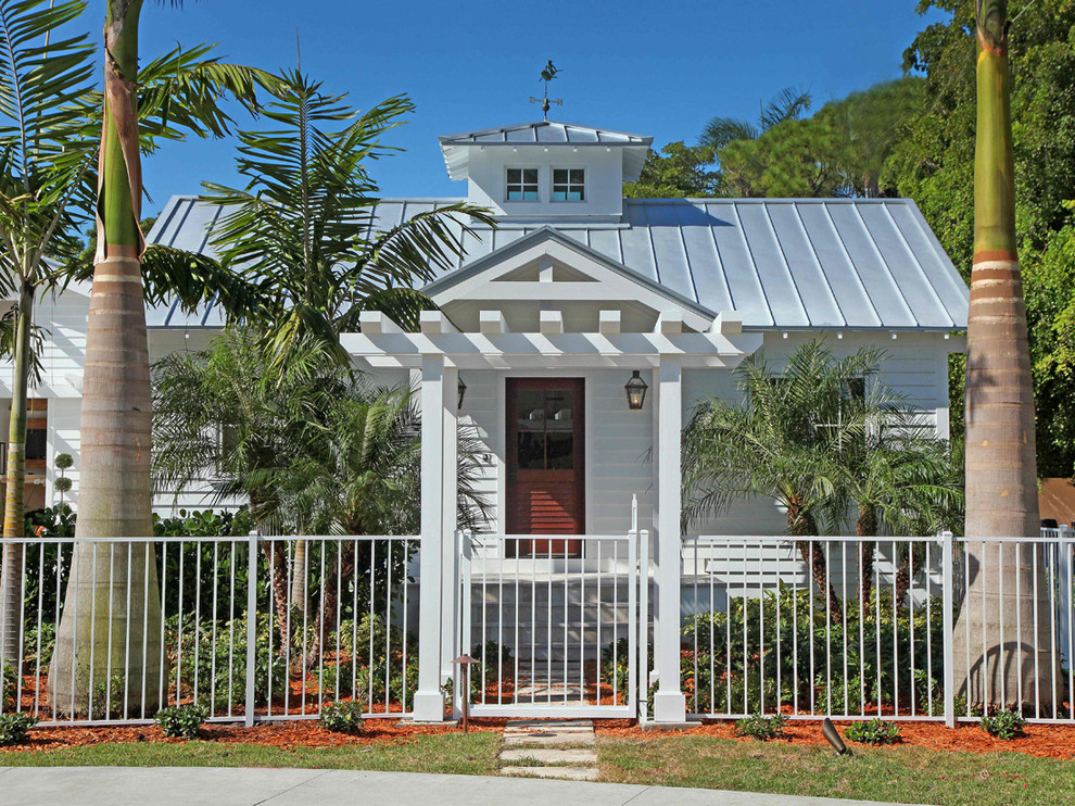 Inspiration for a mid-sized tropical white one-story wood gable roof remodel in Miami with a metal roof