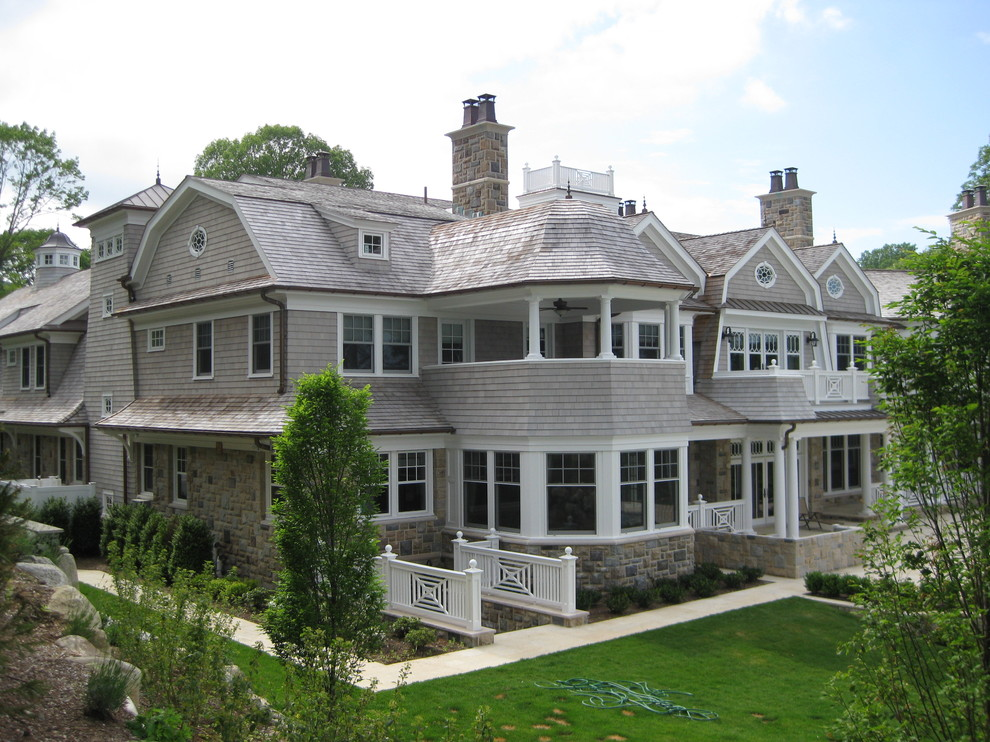 Huge elegant beige stone exterior home photo in Other with a gambrel roof