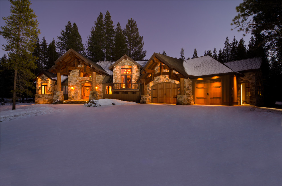 Large rustic brown two-story stone house exterior idea in Other with a hip roof