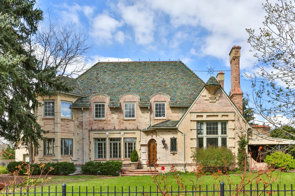 Example of a classic two-story brick exterior home design in Denver with a hip roof