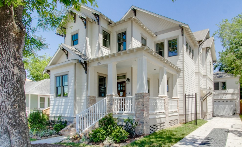 Large traditional white two-story house exterior idea in Houston with a shingle roof