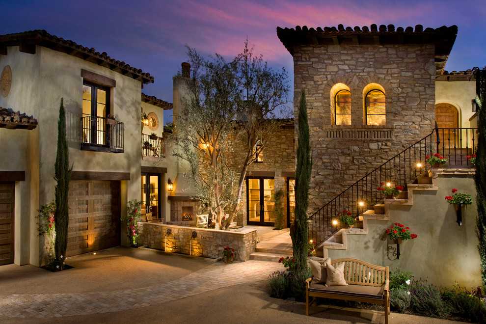 Inspiration for a mediterranean beige two-story house exterior remodel in San Diego with a tile roof